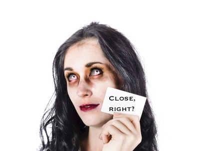 Face of a thoughtful zombie with business card